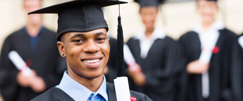 happy african male university graduate with classmates
